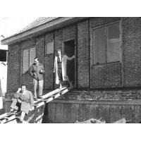 Grażyna i Marian Sztobryn oraz Mirosław Gąsecki przy trzcinowym domku jednorodzinnym przy ul. Polnej budowanym system norweskim przez Spółdzielnię Nauczycielską, Sopot 1957 r.