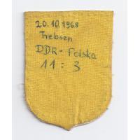 Rewers odznaki z godłem Polski z zapiskami na temat meczu